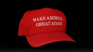 """The iconic red """"Make America Great Again"""" hat against a dark background."""
