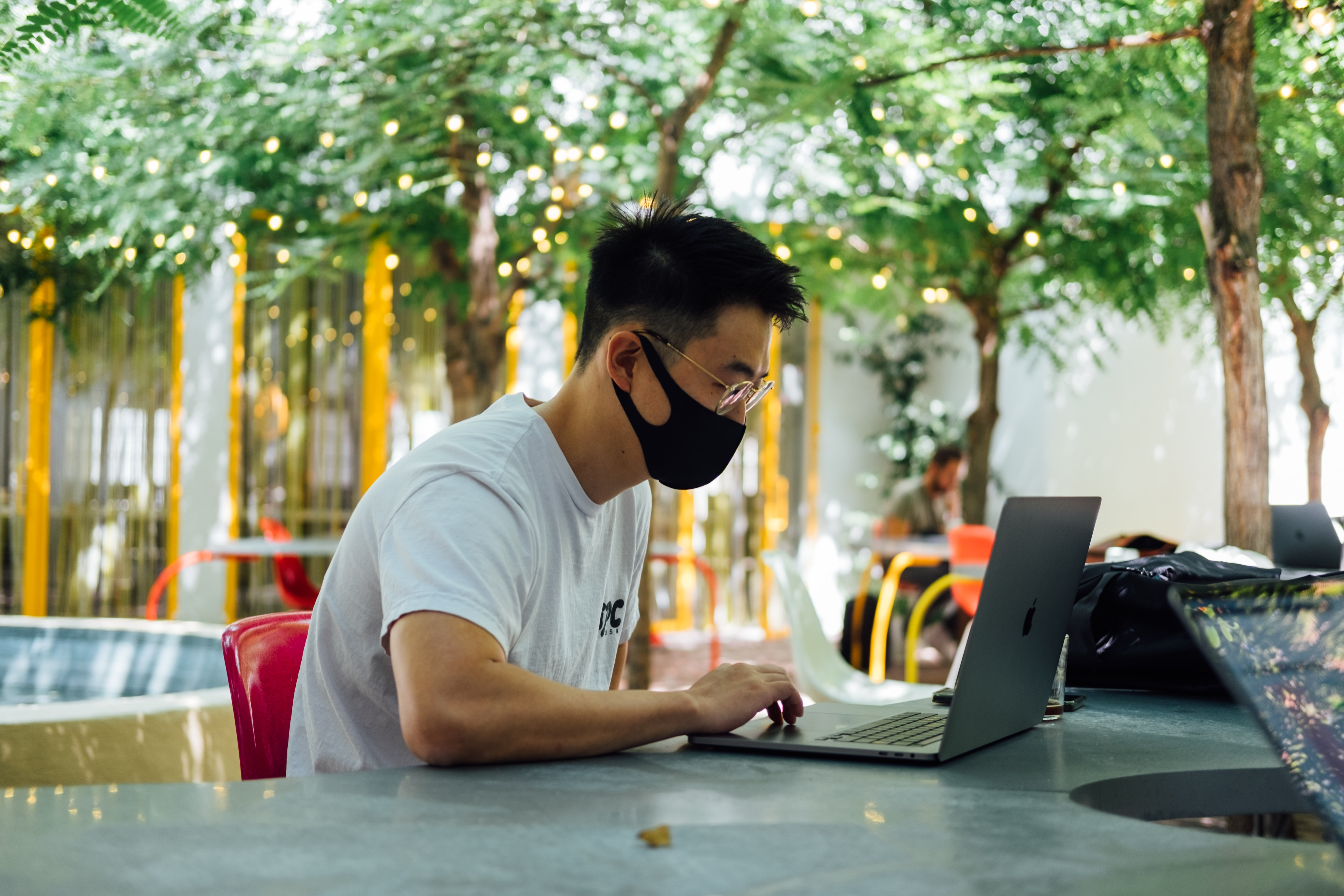 Man in mask working on laptop at outdoor table; image by Paul Hanaoka, via Unsplash.com.