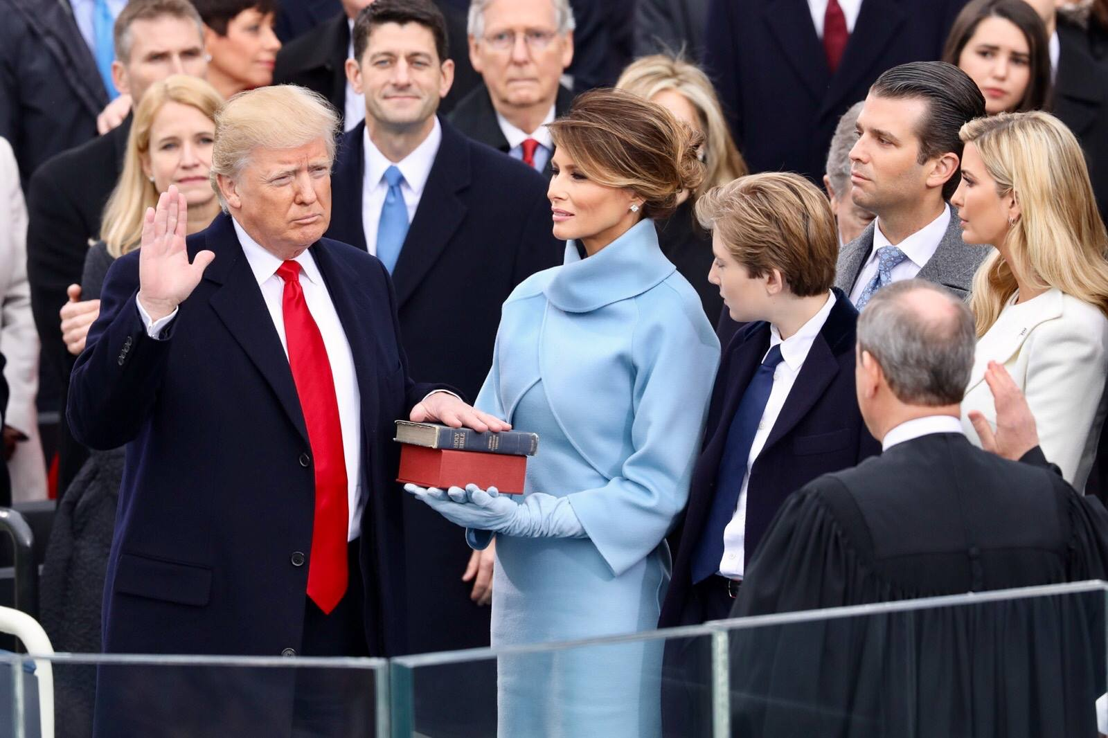 Donald Trump takes the oath of office, hand on two Bibles, with wife Melania, son Barron, and a crowd of others around him.