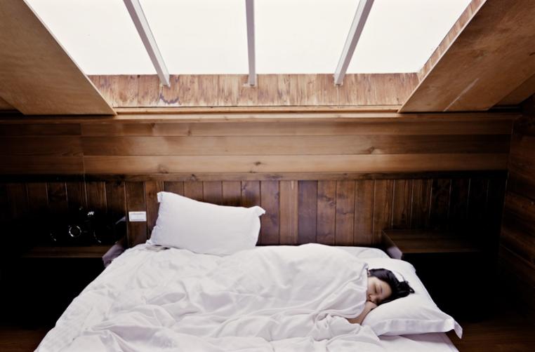 Woman sleeping in bedroom; image by Free-Photos, via Pixabay.com.