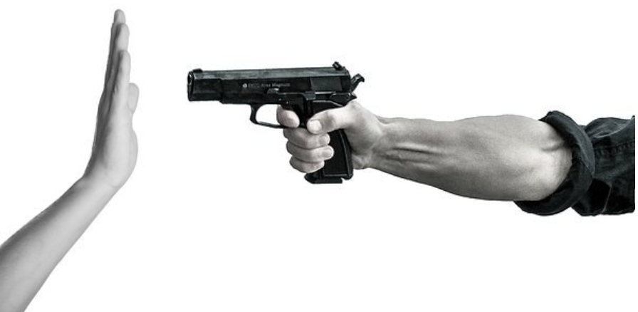 One person pointing a gun, the other raising a hand; image by Tumisu, via Pixabay.com.
