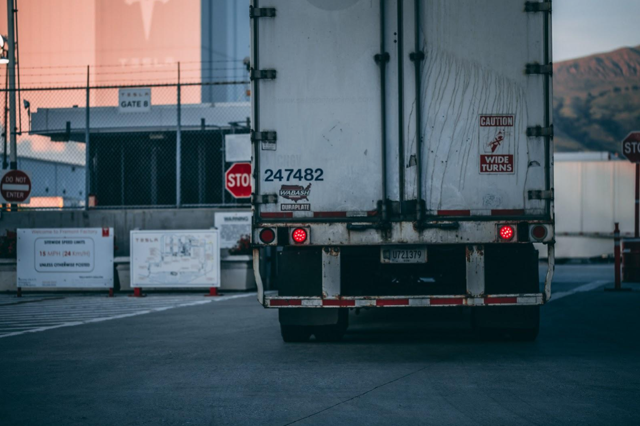 Rear view of a white semi-truck; image by Craig Adderley, via Pexels.com.