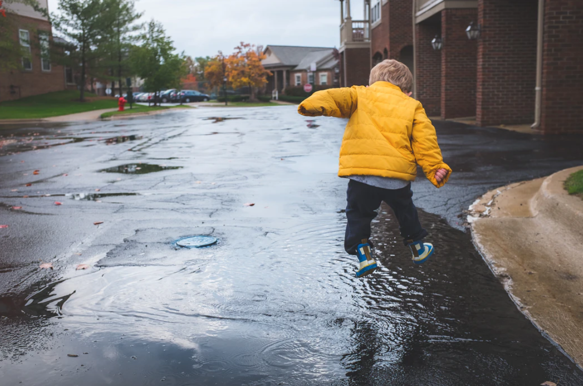 Little boy in yellow jacket jumping in puddle; image by NeONBRAND, via Unsplash.com.