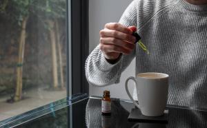 Man putting CBD oil in tea; image by Evopure CBD, via Unsplash.com.