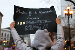 """Person in grey hoodie holding sign saying, """"Girls Just Wanna Have FUNdamental Rights""""; image by Lucia, via Unsplash.com."""