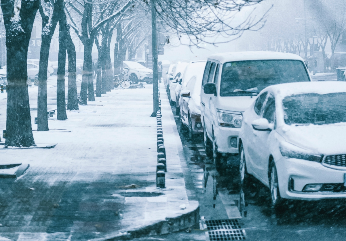Black and white photo of parked vehicles along a winter street; image by Allen Lee, via Unsplash.com.