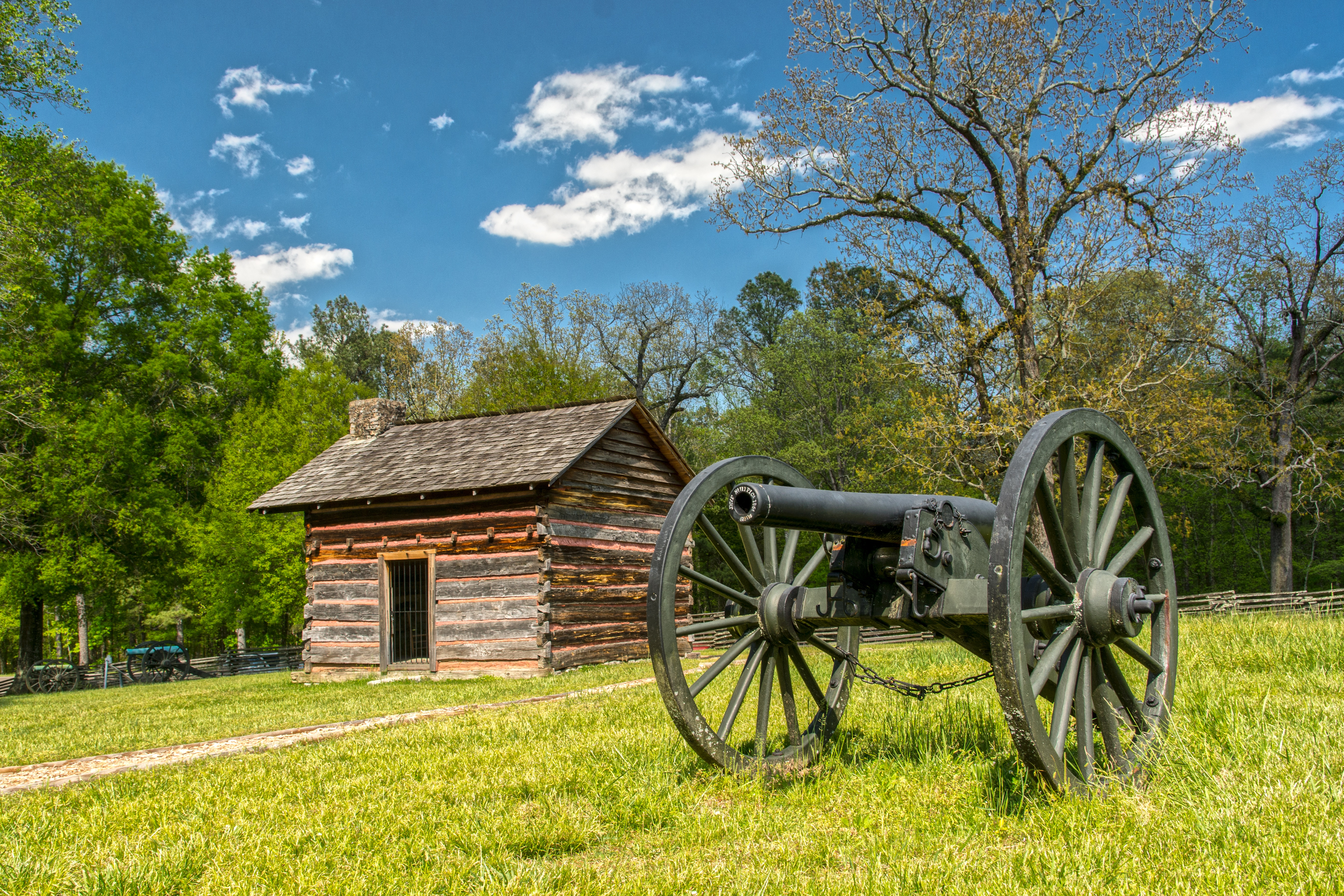 In a green grassy field, an old Civil War cannon sits outside of a small, wooden cabin.