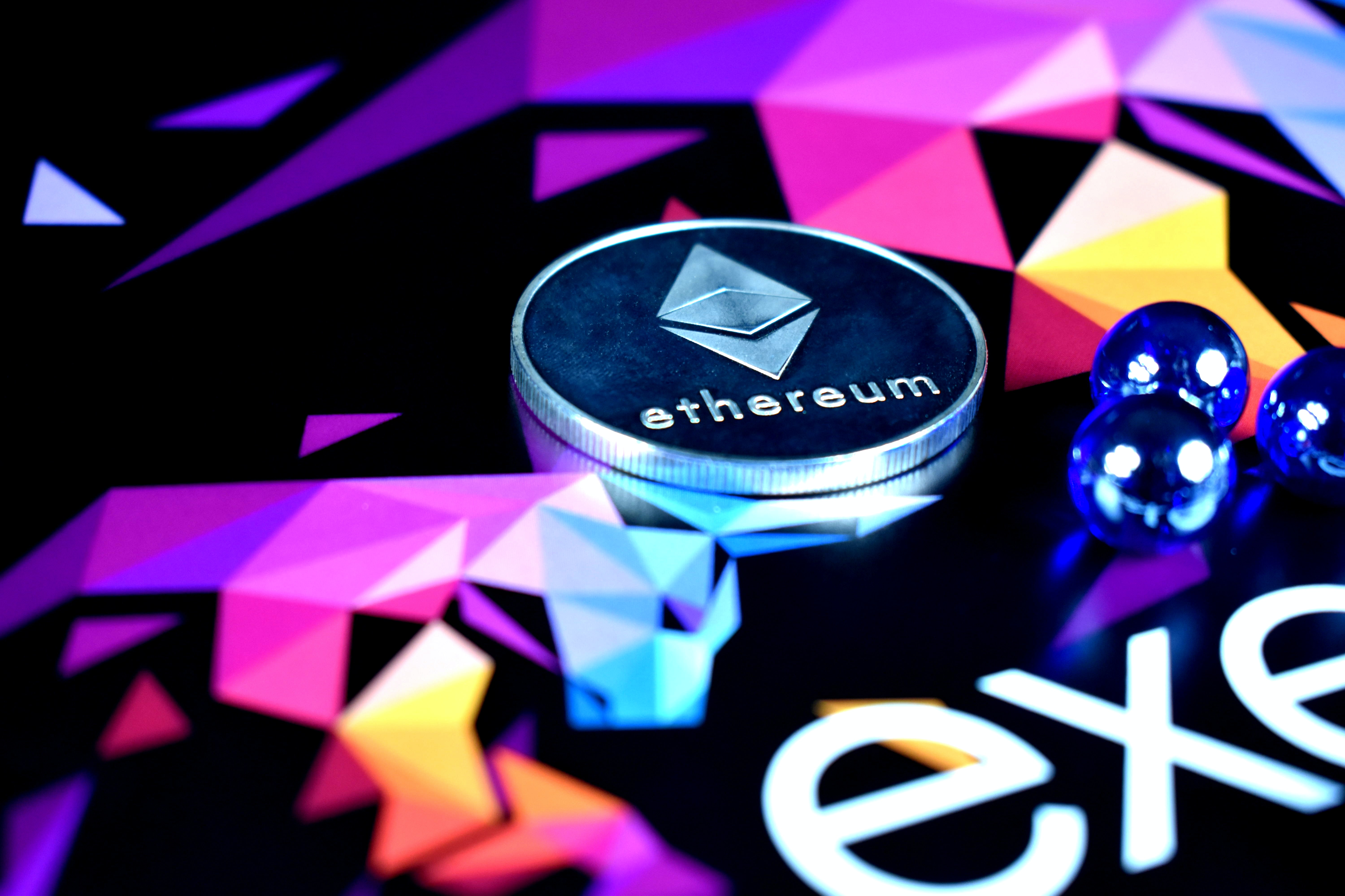 An Ethereum coin being approached by three blue marbles; image by Clifford Photography, via Unsplash.com.