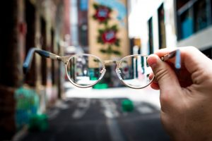 Man holding pair of glasses, surrounding scenery blurry; image by Josh Calabrese, via Unsplash.com.