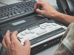 Blind man using a Braille screen reader; image by Sigmund, via Unsplash.com.