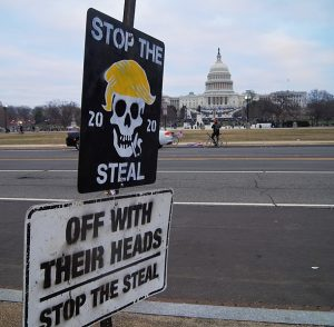 "Roadside protest sign near the Capitol building. It says, ""Stop the Steal"" and ""Off with their heads."""
