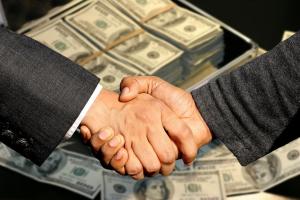 Two men shaking hands over stacks of money; image by Capri23Auto, via Pixabay.com.