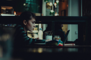 Woman in a cafe, looking at a laptop screen; image by Alex Kalligas, via Unsplash.com.