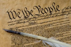 Photo of the Constitution of the United States of America. A feather quill is included in the photo.