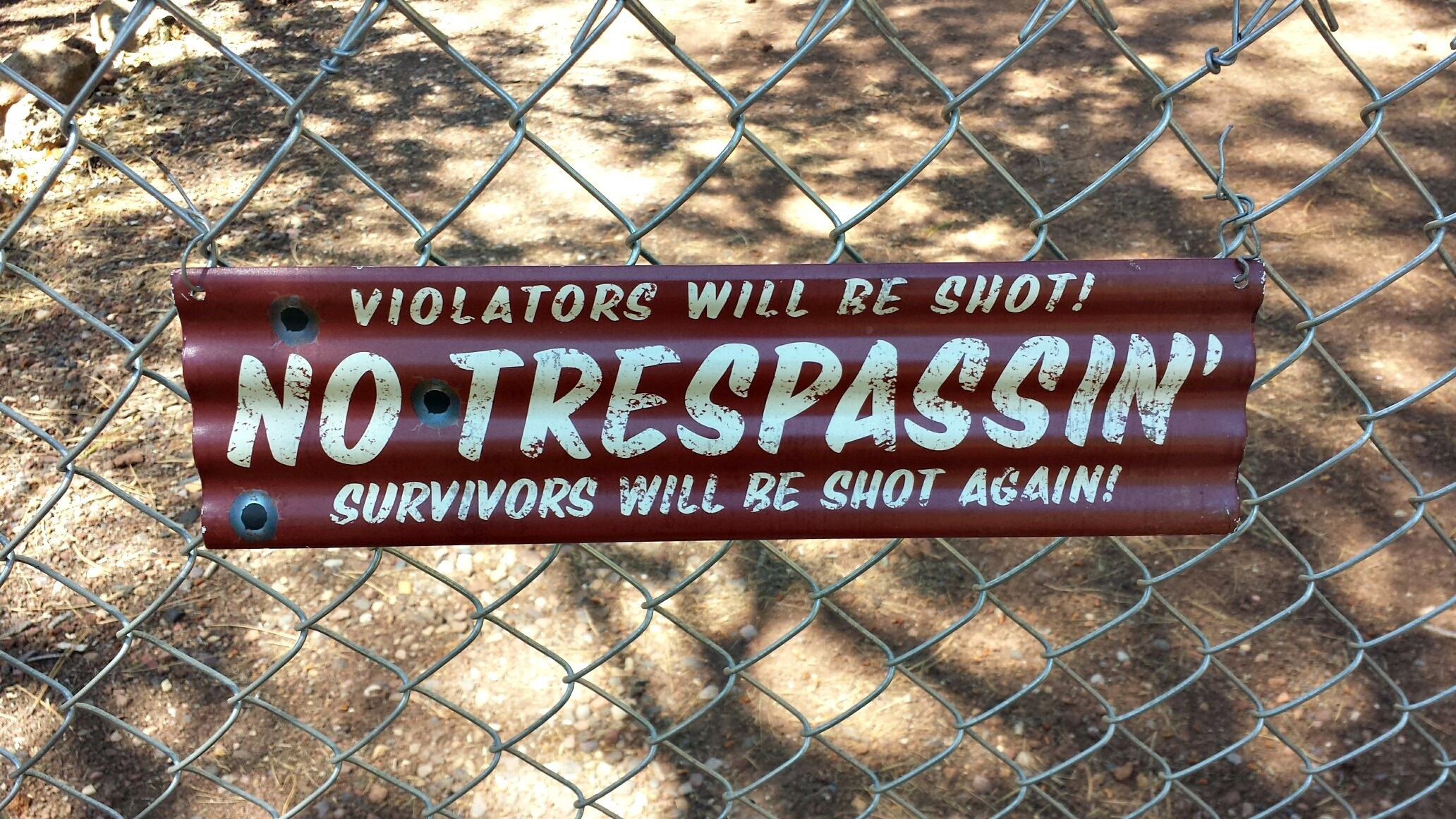 """A sign posted on a fence. It says, """"No Trespassin'. Violators will be shot! Survivors will be shot again!"""""""