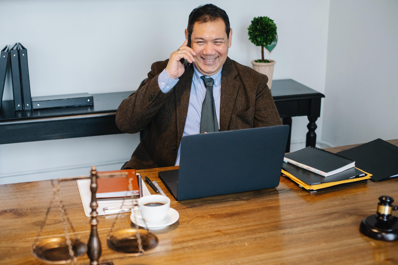 Lawyer at desk talking on smartphone; image by Sora Shimazaki, via Pexels.com.