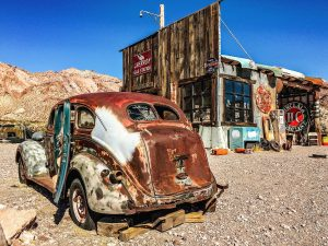An old car rusting away beside an abandoned business in a remote Nevada ghost town.