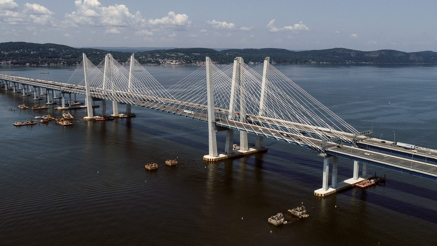Aerial view of a long bridge suspended from cables.