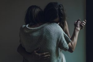 Two women embracing, holding each other close.