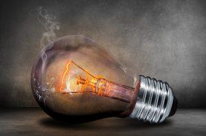 A broken incandescent lightbulb glows dimly against a grey background, emitting a wisp of smoke.