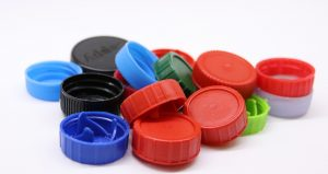 A small collection of differently shaped and colored plastic bottlecaps.