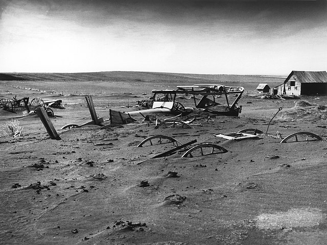 Vintage 1936 photo of Dust Bowl ruination, farm equipment nearly buried under sediment.