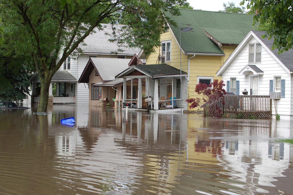 A tree-lined suburban American street with two-story family homes, only it's under several feet of water.