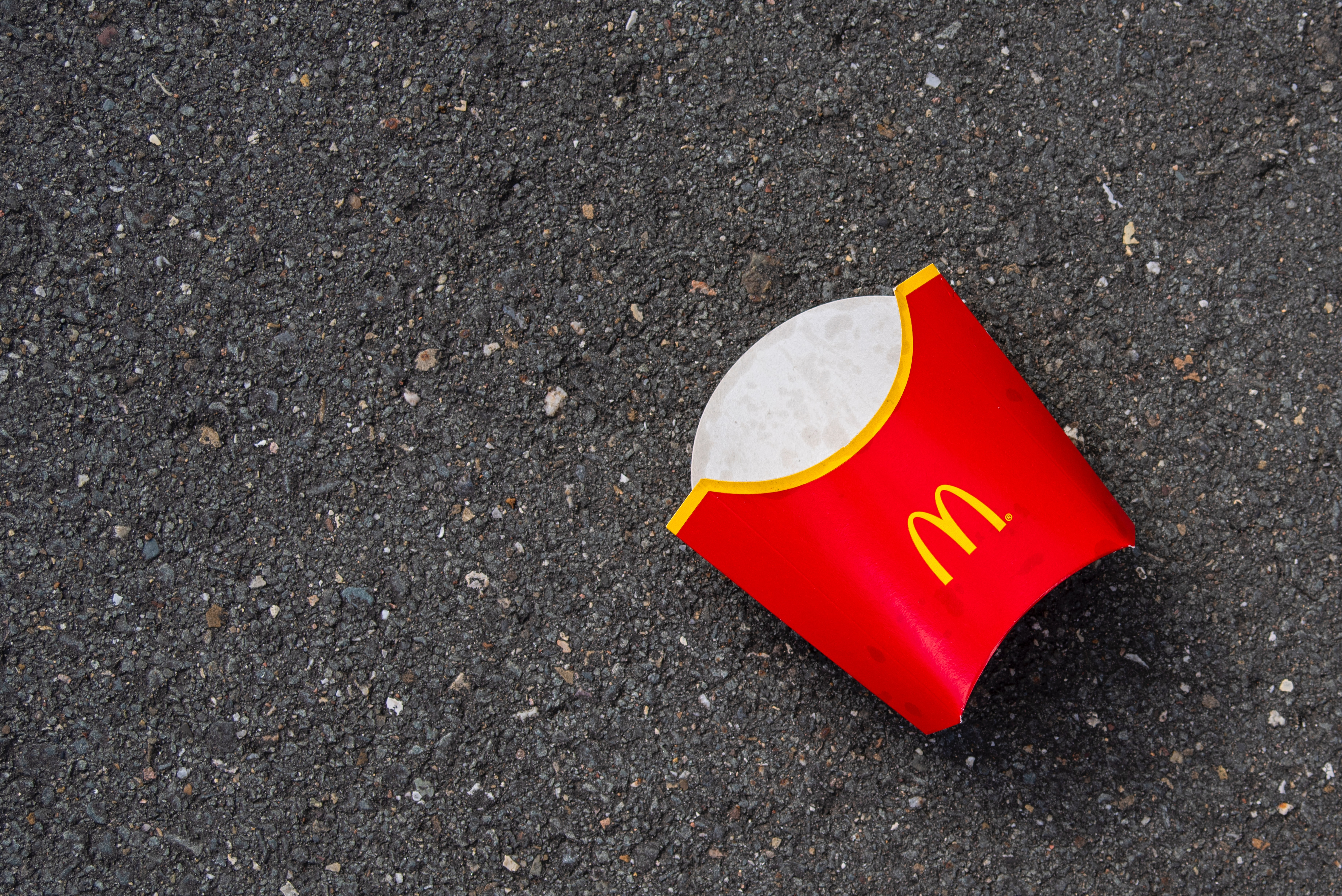 An empty McDonald's French fry sleeve resting on a tarmac surface.