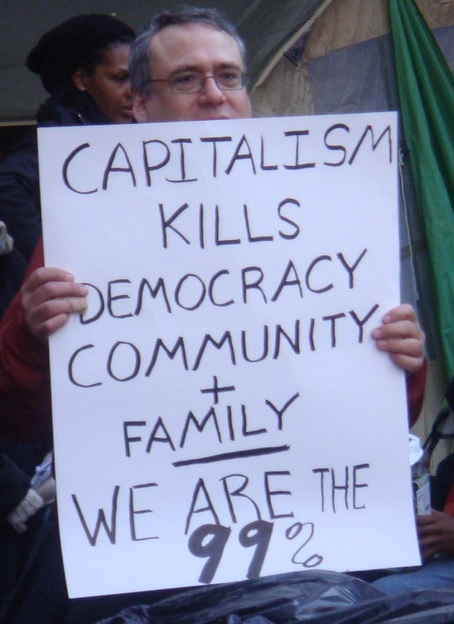 """A man holds a sign that reads, """"Capitalism Kills Democracy Community + Family - We are the 99%"""""""