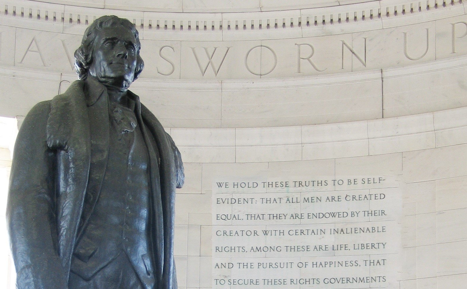 A sculpture of Thomas Jefferson next to the engraved words of the preamble of the Declaration of Independence at the Jefferson Memorial.