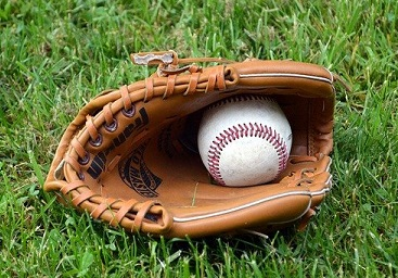 A baseball rests inside of a leather mitt, on grassy ground.