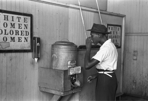 A black man sips from a cup at a segregated drinking area.
