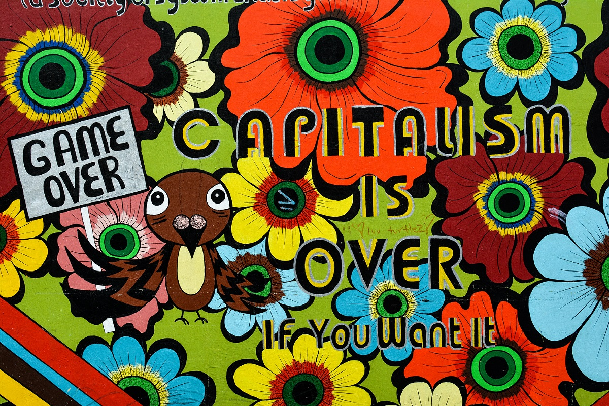 """A colorful wall mural with bright flower images reads, """"Capitalism is Over if You Want It."""""""