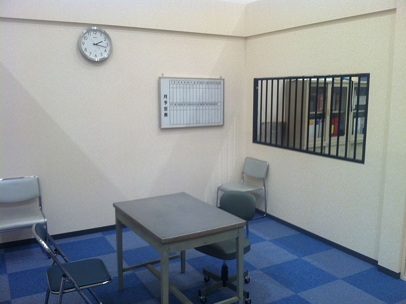 A sparsely furnished room with a tile floor, small table, uncomfortable chairs, a wall clock, and bars on the window.