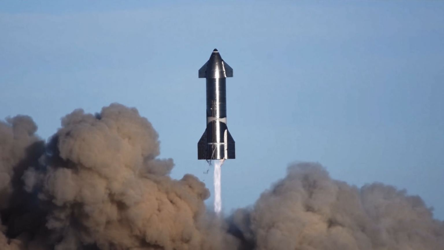 A dark-colored rocket lifts off, with dark, billowing clouds below.