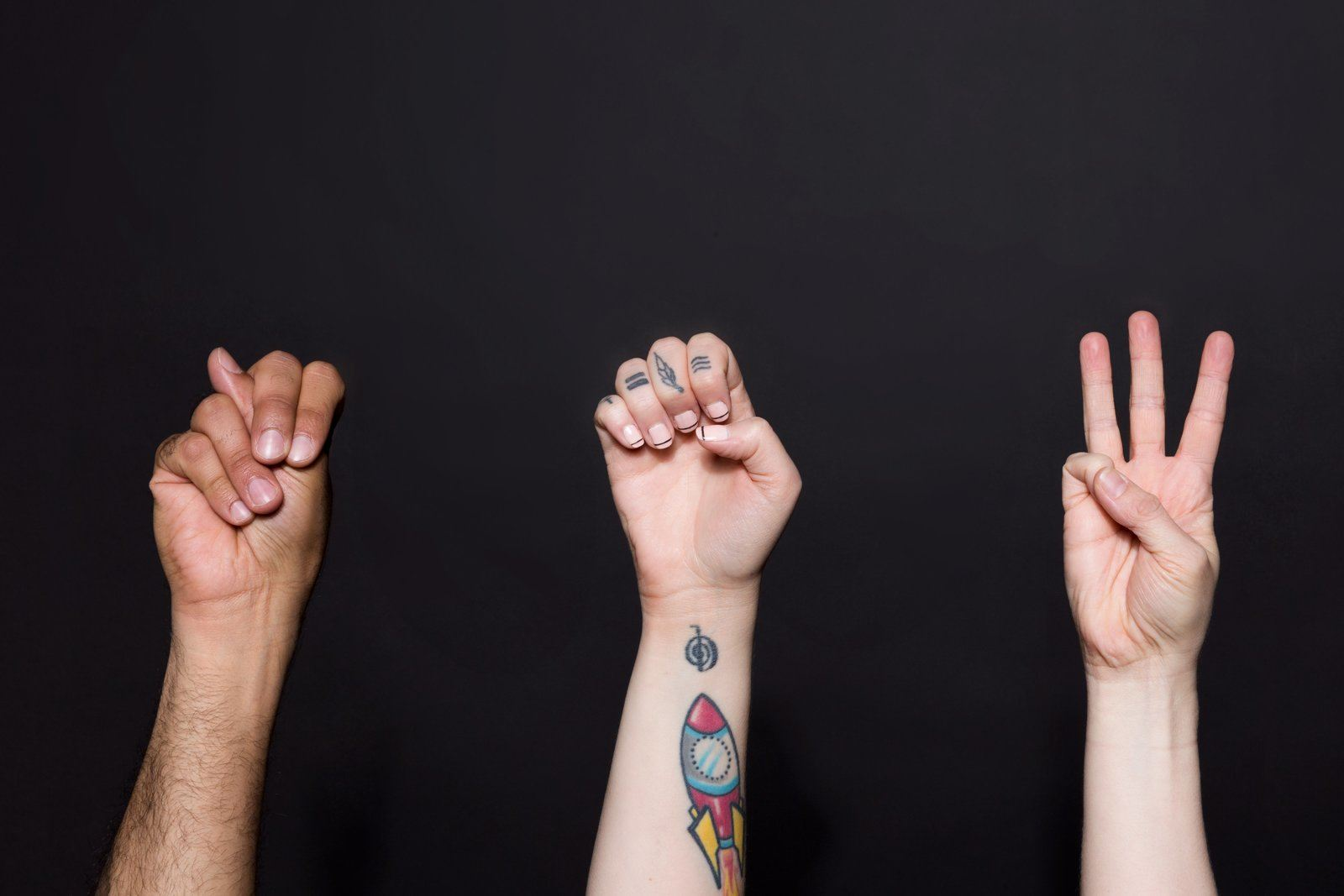"""Three hands sign the word """"NEW."""" Image credit: Sarah Pflug on Wunderstock (license)."""