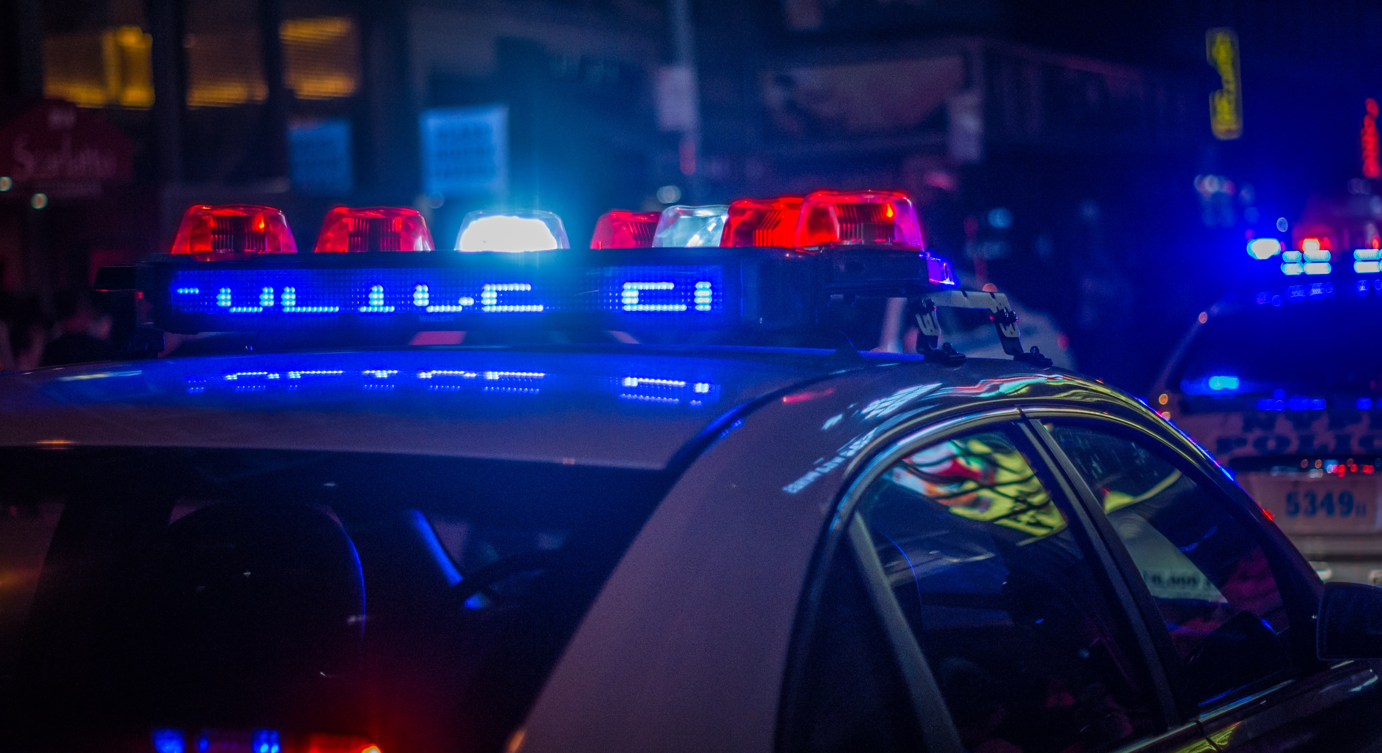 The red and blue flashing lights from a police cruiser in the darkness.
