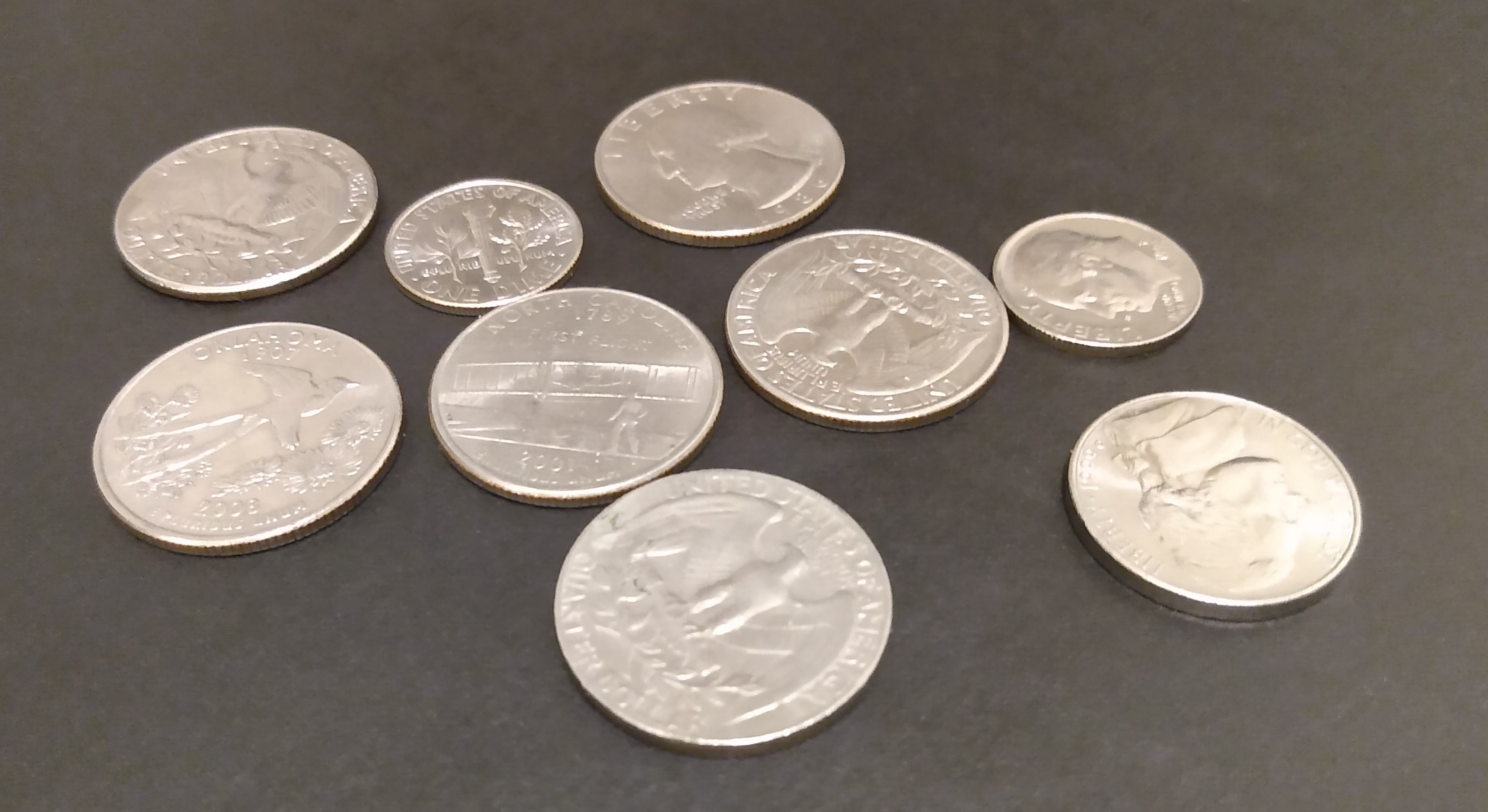 Six quarters, two dimes, and a nickel, on a black background.