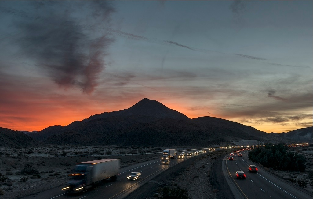 Cars and semi-trucks speed along a freeway at sunset.