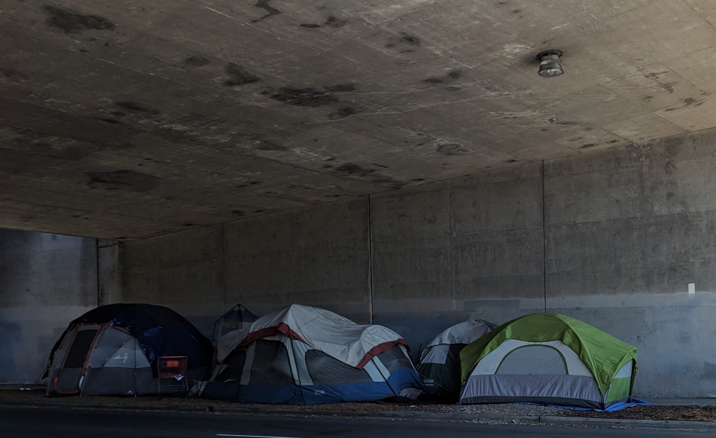 Several tents packed closely together under an overhanging concrete structure.