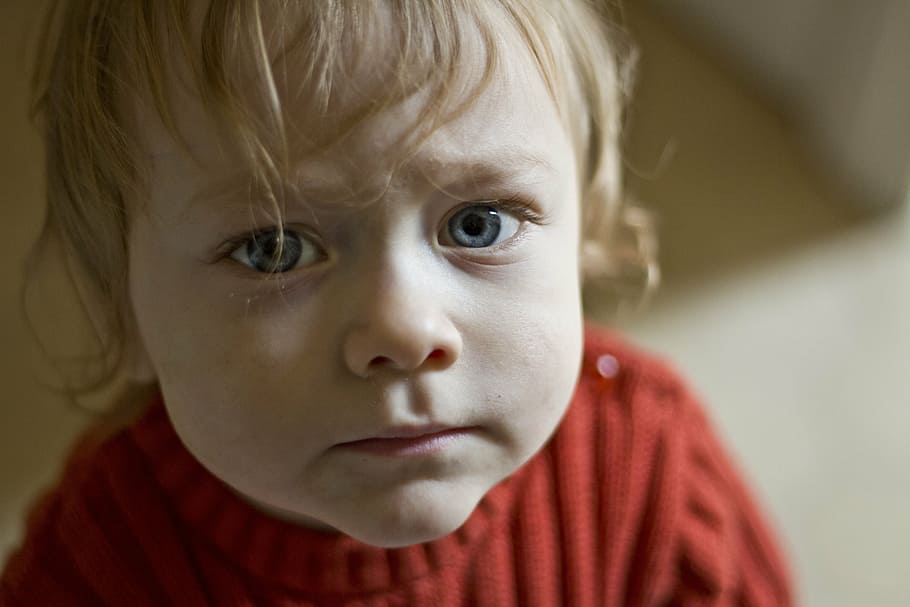 A toddler in a red sweater looks sad.