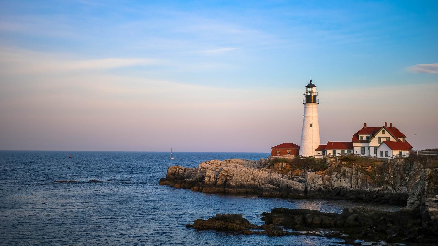 A white lighthouse on a rocky beach near the ocean, at dusk.